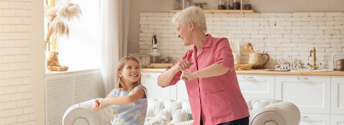 grandparent and child dancing in living room