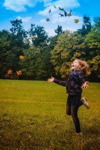 kid in fall leaves