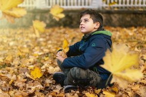 kid sitting in leaves