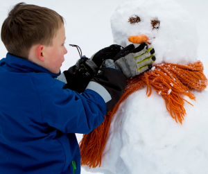 kid building snowman