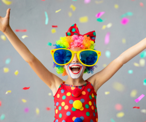 kid dressed as clown with big glasses, big smile and arms up
