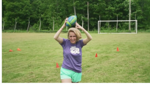 camper throwing a ball in an obstacle course